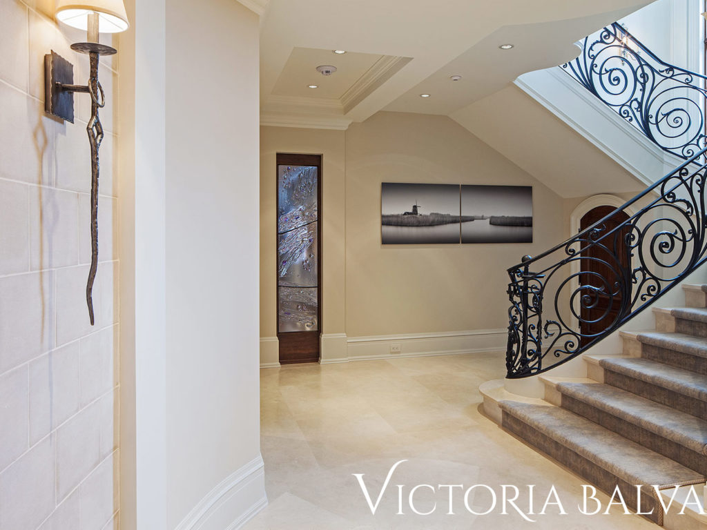 Staircase landing and view of the hall with accent cast art wall divider