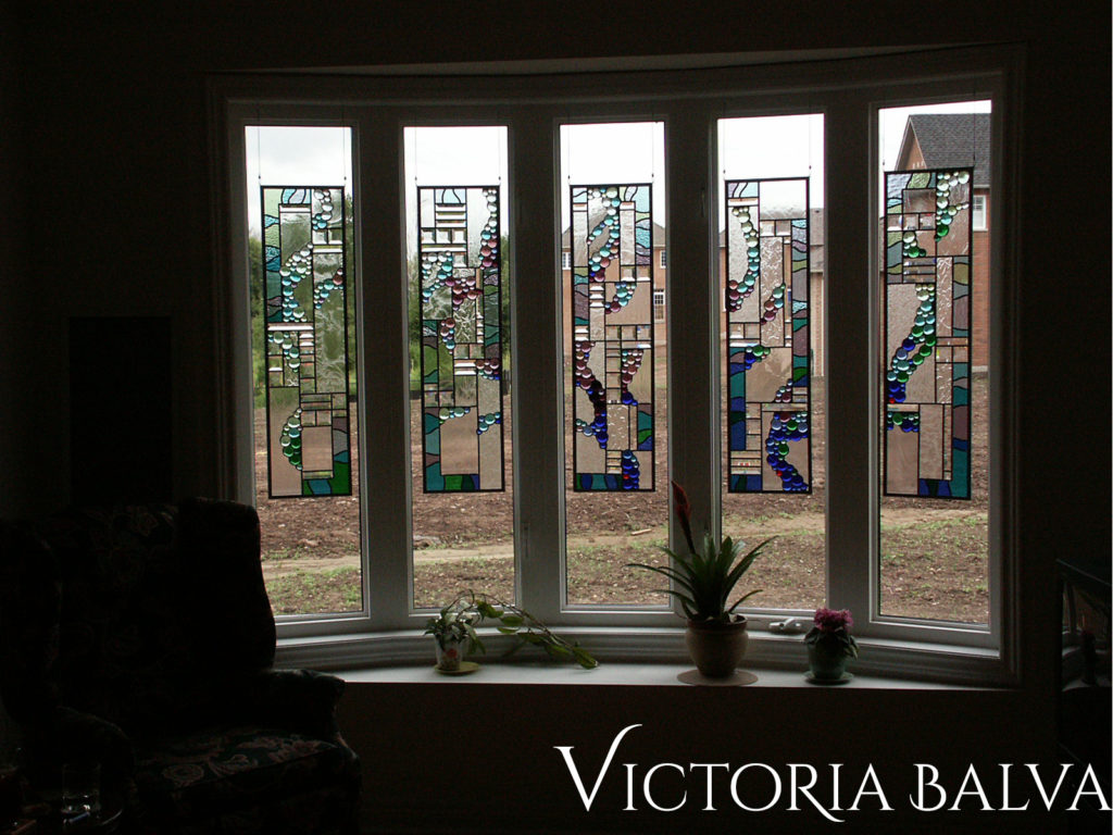 Contemporary style stained and leaded glass panels suspended in a bay window of the family room in Burlington