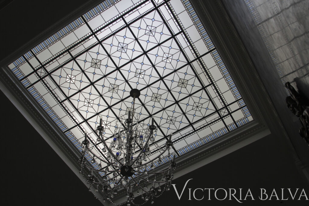 Large stained and leaded glass skylight ceiling with custom hand beveled glass and crystal chandelier. Interior design by Timothy Mather Design