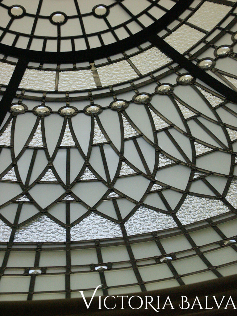 Residential stained glass dome illuminated in the evening with jewels and bevelled glass