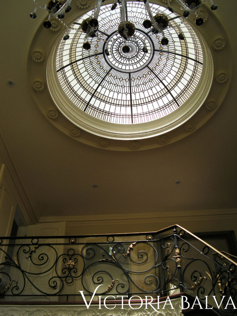 Double height atrium foyer with stained and leaded glass dome chandelier
