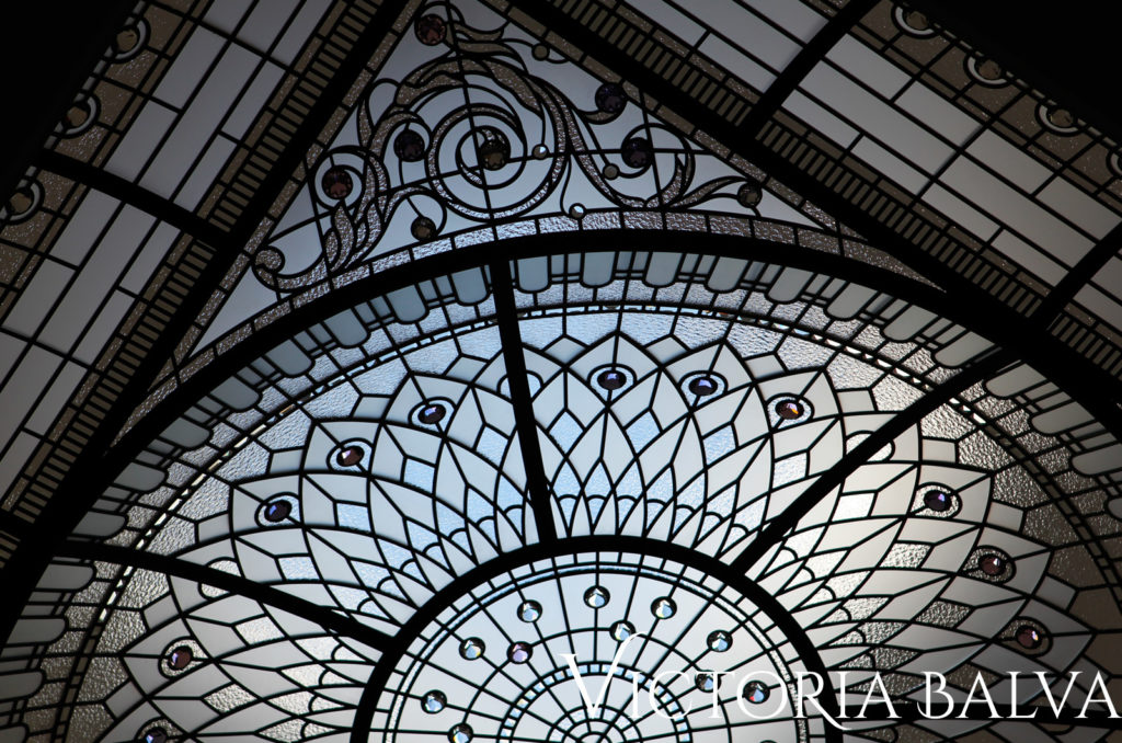 Classic atrium stained and leaded glass domed ceiling with acanthus leaves ornaments and geometric pattern