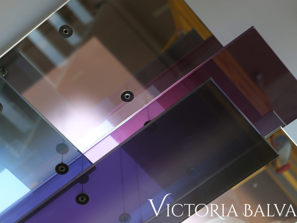 Laminated reflective coloured glass suspension