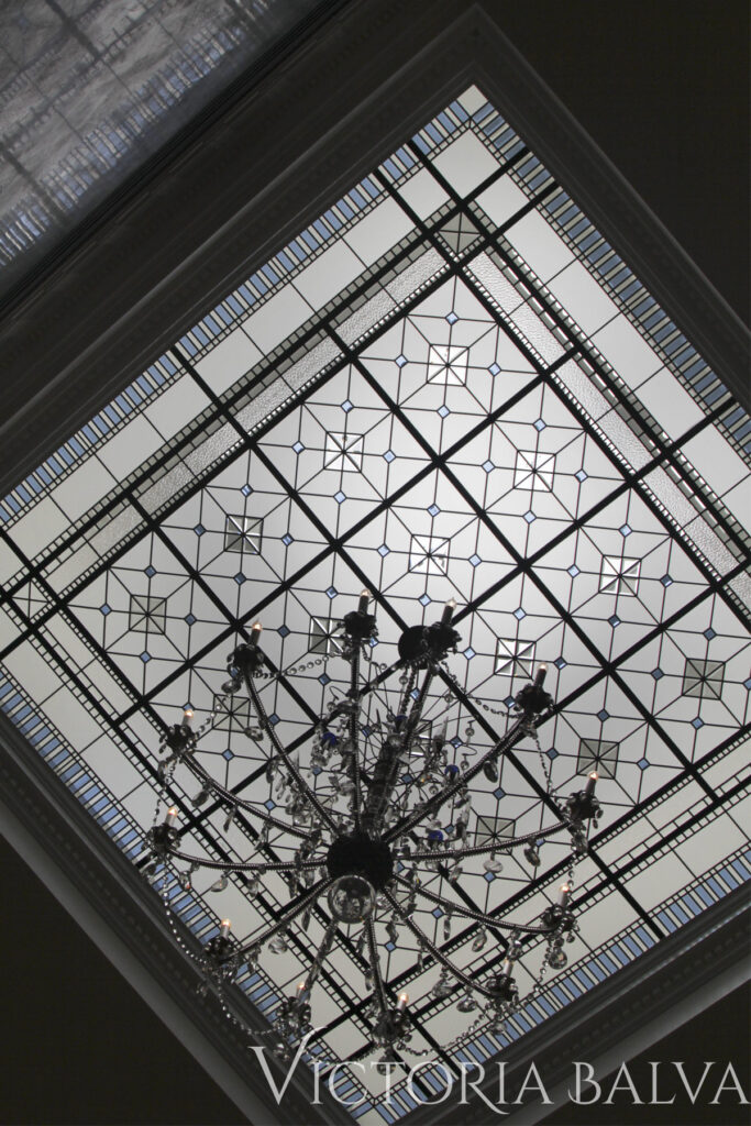 Large stained and leaded glass skylight with colored beveled glass and crystal chandelier with gray Venetian plaster accent wall