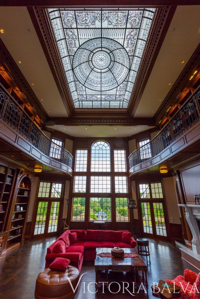 Double height great room with the library with large stained and leaded glass domed skylight for custom built residence