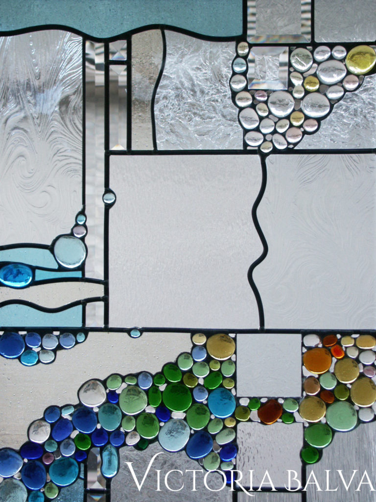 Modern abstract art glass window with coloured globes and bevelled glass glass