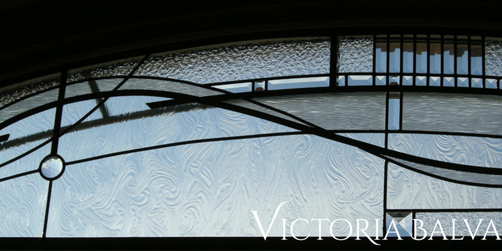 Close up detail of modern stained and leaded glass transom with artistic linesand clear textured stained glasses
