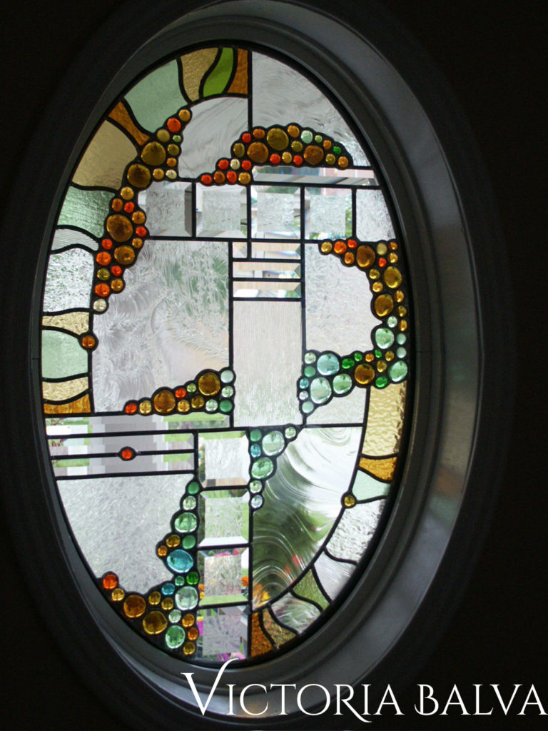 Modern design stained and leaded glass oval window with glass nuggets and clear glue chip bevelled glass