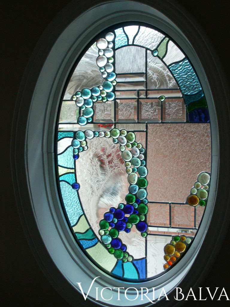 Modern stained and leaded glass oval window for a front entrance foyer with bevelled glass and nuggets