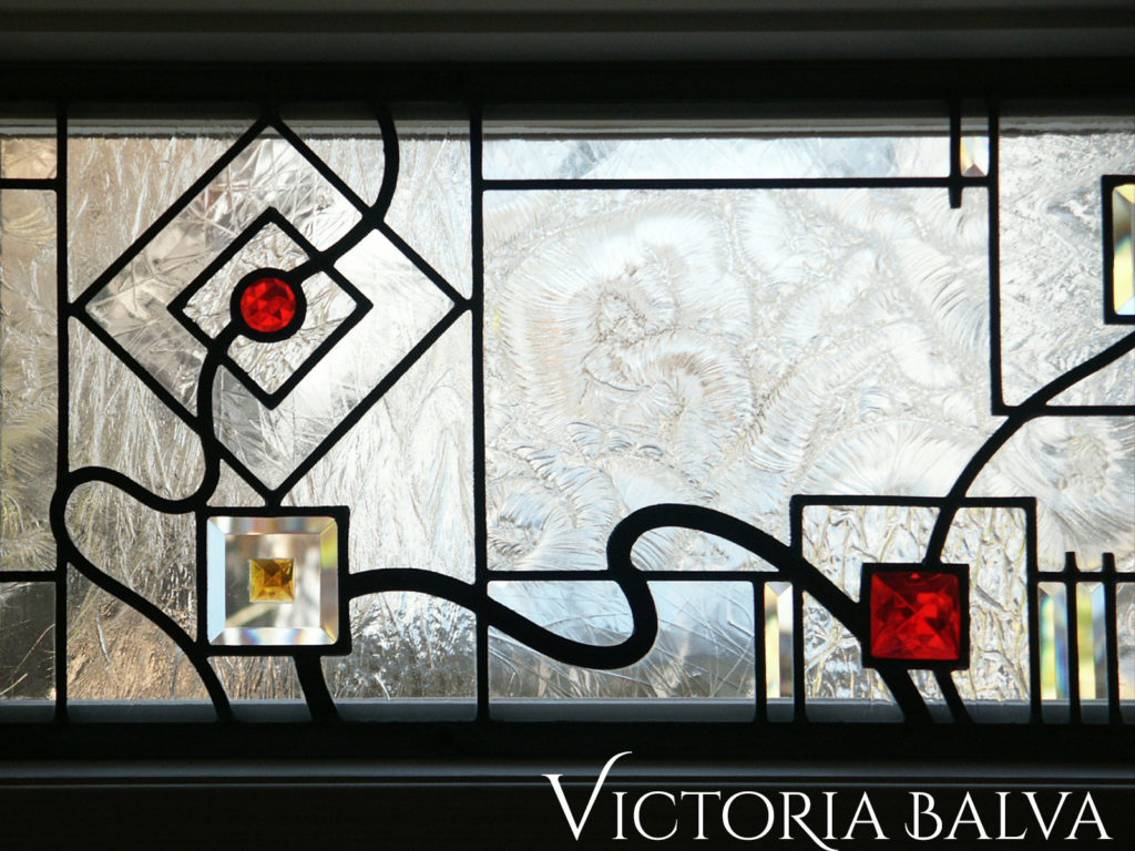 Abstract modern stained glass windoe with clear textured glass, red jewels and clear beveled glass