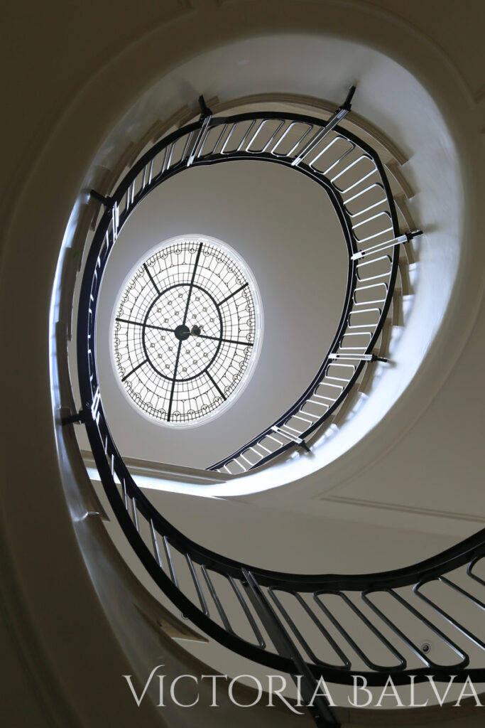 An oval staircase with oval stained and leaded glass dome. Interior design by Timothy Mather Design