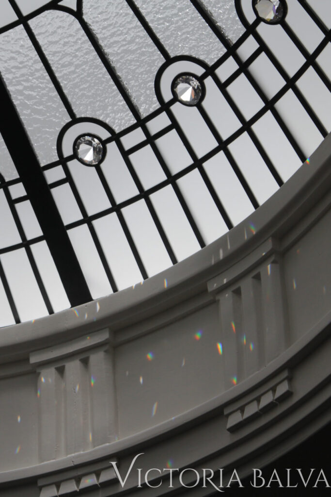 Clear crystal glass border of stained and leaded glass dome skylight with refracted light from jewels and bevelled glass. Interior design by Timothy Mather Design