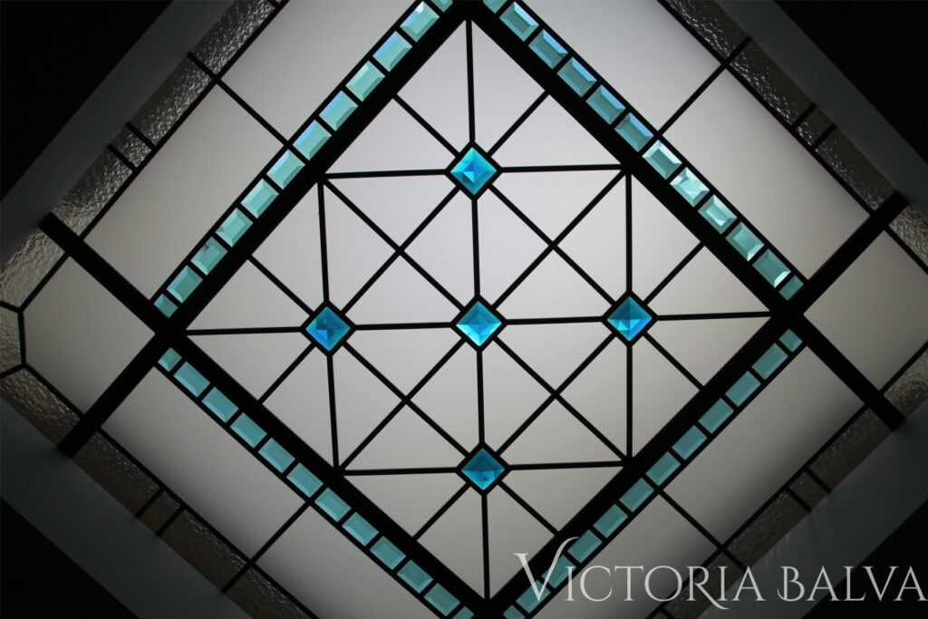 Small octagon stained and leaded glass skylight with turquoise hand beveled glass and crystal stained glass jewels for a hallway of a custom built home