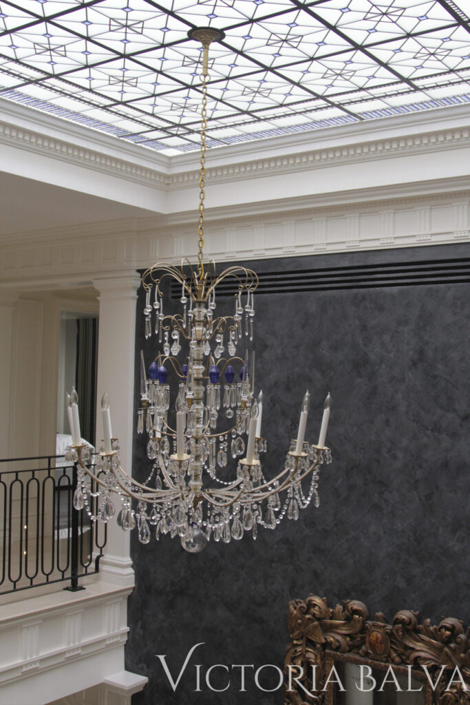 Crystal chandelier hanging from glass ceiling of a great room. Interior design by Timothy Mather Design