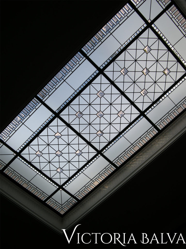 Large leaded glass skylight with clear and coloured bevelled glass and coloured accent jewels