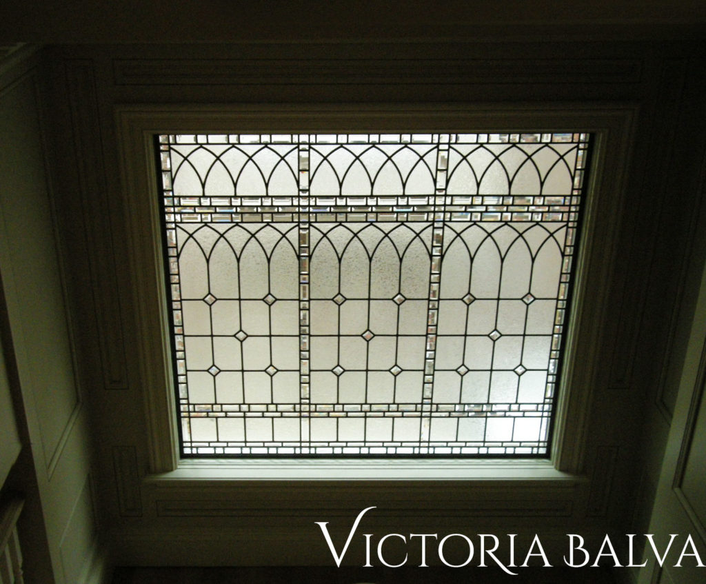 Decorative stained and leaded glass landing window for a renovated house by Merit Homes in Toronto